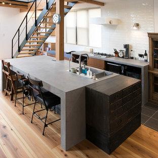 他の地域のアジアンスタイルのおしゃれなキッチン (ドロップインシンク、フラットパネル扉のキャビネット、中間色木目調キャビネット、白いキッチンパネル、グレーの床、グレーのキッチンカウンター) の写真
