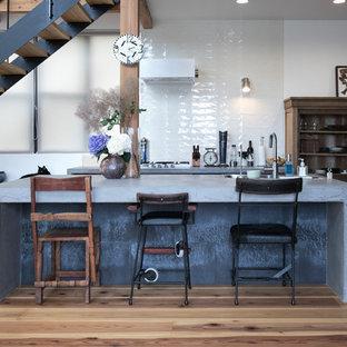 他の地域のエクレクティックスタイルのおしゃれなキッチン (シングルシンク、コンクリートカウンター、白いキッチンパネル、セラミックタイルのキッチンパネル、無垢フローリング、茶色い床、グレーのキッチンカウンター) の写真