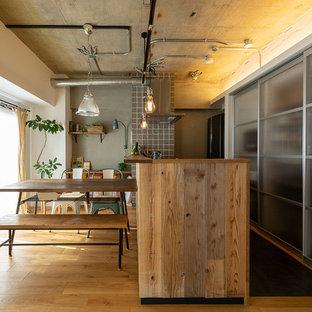 他の地域のインダストリアルスタイルのおしゃれなキッチン (茶色い床、ガラス扉のキャビネット、グレーのキッチンパネル、無垢フローリング) の写真