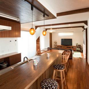 他の地域のアジアンスタイルのおしゃれなキッチン (シングルシンク、ステンレスカウンター、無垢フローリング、茶色い床) の写真