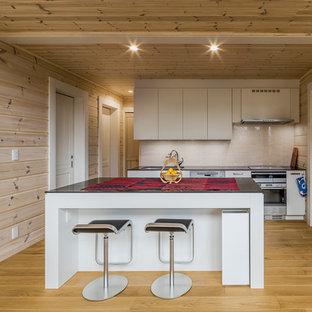 他の地域の北欧スタイルのおしゃれなキッチン (シングルシンク、フラットパネル扉のキャビネット、白いキャビネット、ベージュキッチンパネル、無垢フローリング、茶色い床) の写真
