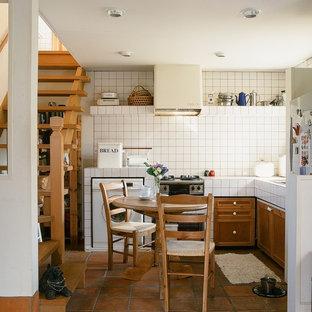 Kleine Country Wohnküche ohne Insel in L-Form mit profilierten Schrankfronten, hellbraunen Holzschränken, Arbeitsplatte aus Fliesen, weißen Elektrogeräten und Backsteinboden in Sonstige