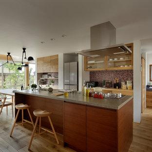 他の地域のカントリー風おしゃれなキッチン (シングルシンク、フラットパネル扉のキャビネット、中間色木目調キャビネット、無垢フローリング、茶色い床) の写真