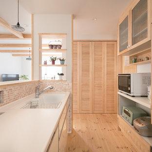 Modelo de cocina de galera, campestre, abierta, con armarios con paneles lisos, puertas de armario de madera clara, electrodomésticos de acero inoxidable, suelo de madera clara y suelo beige