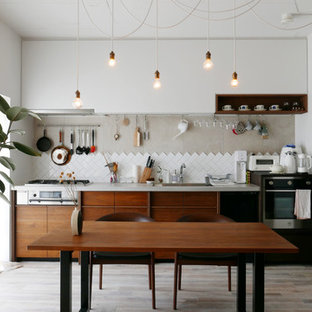 Imagen de cocina lineal, minimalista, abierta, con fregadero bajoencimera, puertas de armario de madera en tonos medios, encimera de azulejos, salpicadero beige, salpicadero de azulejos de cerámica, electrodomésticos de acero inoxidable, suelo de madera clara, suelo blanco y encimeras grises