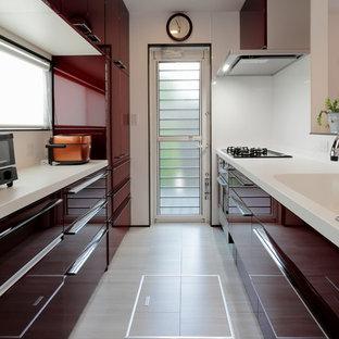 東京23区のコンテンポラリースタイルのおしゃれなキッチン (一体型シンク、フラットパネル扉のキャビネット、赤いキャビネット、白いキッチンパネル、クッションフロア、グレーの床、白いキッチンカウンター) の写真