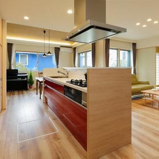 東京23区のモダンスタイルのおしゃれなキッチン (シングルシンク、フラットパネル扉のキャビネット、赤いキャビネット、白いキッチンパネル、淡色無垢フローリング、ベージュの床) の写真