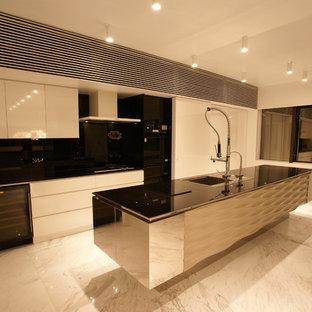 東京都下のコンテンポラリースタイルのおしゃれなキッチン (ドロップインシンク、フラットパネル扉のキャビネット、白いキャビネット、黒い調理設備) の写真