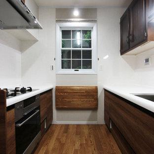 東京都下の小さいカントリー風おしゃれなII型キッチン (フラットパネル扉のキャビネット、濃色木目調キャビネット、人工大理石カウンター、茶色いキッチンパネル、茶色いキッチンカウンター) の写真