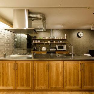 福岡のインダストリアルスタイルのおしゃれなキッチン (シングルシンク、落し込みパネル扉のキャビネット、中間色木目調キャビネット、ステンレスカウンター、無垢フローリング、茶色い床) の写真
