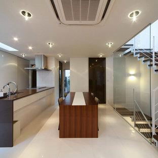 他の地域のモダンスタイルのおしゃれなキッチン (アンダーカウンターシンク、フラットパネル扉のキャビネット、白いキャビネット、クオーツストーンカウンター、白いキッチンパネル、磁器タイルのキッチンパネル、パネルと同色の調理設備、磁器タイルの床、白い床) の写真