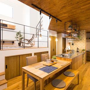 Idéer för orientaliska linjära kök med öppen planlösning, med bänkskiva i rostfritt stål, mellanmörkt trägolv, en undermonterad diskho, släta luckor, skåp i mellenmörkt trä, rostfria vitvaror och en halv köksö