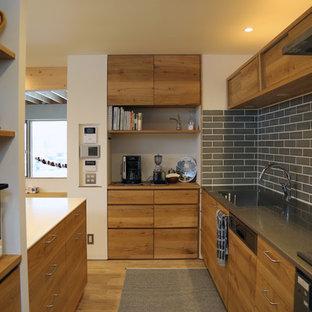 札幌の北欧スタイルのおしゃれなキッチン (シングルシンク、フラットパネル扉のキャビネット、中間色木目調キャビネット、ステンレスカウンター、グレーのキッチンパネル、セラミックタイルのキッチンパネル、淡色無垢フローリング、茶色い床) の写真