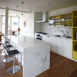他の地域のモダンスタイルのおしゃれなキッチン (シングルシンク、フラットパネル扉のキャビネット、白いキャビネット、大理石カウンター、白いキッチンパネル、セラミックタイルのキッチンパネル、無垢フローリング、茶色い床) の写真