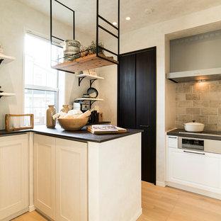 横浜のエクレクティックスタイルのおしゃれなキッチン (落し込みパネル扉のキャビネット、白いキャビネット、ベージュキッチンパネル、塗装フローリング、ベージュの床、黒いキッチンカウンター) の写真