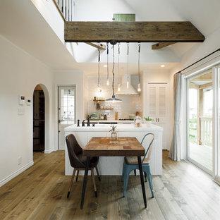 他の地域のカントリー風おしゃれなキッチン (白いキャビネット、無垢フローリング、茶色い床) の写真