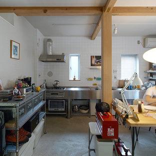 他の地域のインダストリアルスタイルのおしゃれなキッチン (一体型シンク、オープンシェルフ、ステンレスカウンター、コンクリートの床、白いキッチンパネル、シルバーの調理設備の、グレーの床) の写真