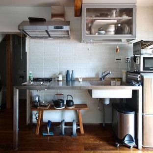 東京23区の小さいインダストリアルスタイルのおしゃれなキッチン (オープンシェルフ、ステンレスカウンター、白いキッチンパネル、茶色い床、一体型シンク、シルバーの調理設備の、濃色無垢フローリング) の写真