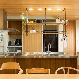 他の地域の広いインダストリアルスタイルのおしゃれなキッチン (ステンレスカウンター、白いキッチンパネル、ボーダータイルのキッチンパネル、無垢フローリング、茶色い床、茶色いキッチンカウンター、シングルシンク) の写真