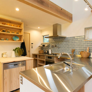 横浜のアジアンスタイルのおしゃれなL型キッチン (シングルシンク、オープンシェルフ、ステンレスカウンター、青いキッチンパネル、無垢フローリング、茶色い床) の写真