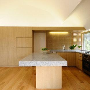 アジアンスタイルのおしゃれなキッチン (アンダーカウンターシンク、フラットパネル扉のキャビネット、淡色木目調キャビネット、ベージュキッチンパネル、シルバーの調理設備、淡色無垢フローリング、ベージュの床) の写真