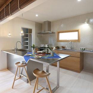 他の地域のII型モダンスタイルのキッチンの画像 (フラットパネル扉のキャビネット、淡色木目調キャビネット、モザイクタイルのキッチンパネル、シルバーの調理設備、淡色無垢フローリング、ペニンシュラ型)