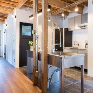 札幌のインダストリアルスタイルのおしゃれなキッチン (シングルシンク、フラットパネル扉のキャビネット、グレーのキャビネット、ステンレスカウンター、グレーの床) の写真