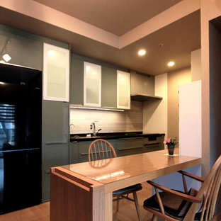 Mid-sized modern galley open plan kitchen in Tokyo with an undermount sink, flat-panel cabinets, green cabinets, solid surface benchtops, beige splashback, matchstick tile splashback, black appliances, plywood floors and black benchtop.