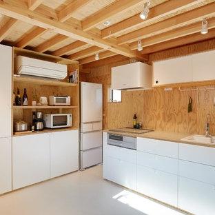 Idéer för små orientaliska linjära grått kök med öppen planlösning, med vita skåp, vitt stänkskydd, stänkskydd i trä, rostfria vitvaror och vitt golv