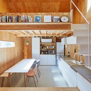東京23区の小さいアジアンスタイルのおしゃれなキッチン (白いキャビネット、アイランドなし、グレーのキッチンカウンター、ドロップインシンク、フラットパネル扉のキャビネット、茶色いキッチンパネル、木材のキッチンパネル、白い調理設備、白い床) の写真