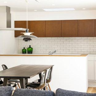 他の地域のアジアンスタイルのおしゃれなキッチン (フラットパネル扉のキャビネット、濃色木目調キャビネット、白いキッチンパネル、レンガのキッチンパネル、淡色無垢フローリング、ベージュの床、白いキッチンカウンター) の写真