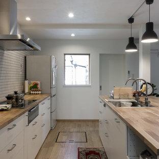 Geräumige, Offene, Zweizeilige Skandinavische Küche mit Arbeitsplatte aus Holz, Küchengeräten aus Edelstahl, Kücheninsel, beigem Boden, Waschbecken, flächenbündigen Schrankfronten, weißen Schränken und gebeiztem Holzboden in Kyoto