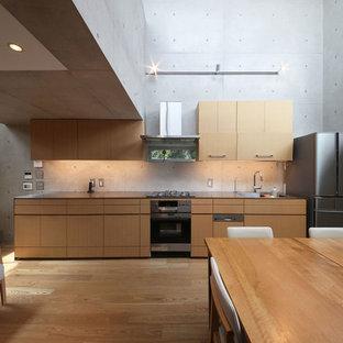 東京23区のモダンスタイルのおしゃれなキッチン (シングルシンク、フラットパネル扉のキャビネット、中間色木目調キャビネット、ステンレスカウンター、グレーのキッチンパネル、シルバーの調理設備、無垢フローリング、茶色い床) の写真