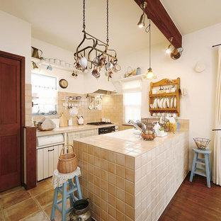 東京23区の地中海スタイルのおしゃれなキッチン (シングルシンク、タイルカウンター、ベージュキッチンパネル、セラミックタイルのキッチンパネル、テラコッタタイルの床、茶色い床、ベージュのキッチンカウンター) の写真