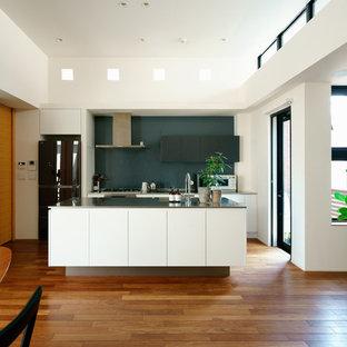 名古屋のコンテンポラリースタイルのおしゃれなキッチン (シングルシンク、フラットパネル扉のキャビネット、白いキャビネット、ステンレスカウンター、黒い調理設備、無垢フローリング、茶色い床) の写真