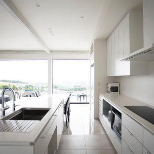 他の地域のコンテンポラリースタイルのおしゃれなキッチン (シングルシンク、フラットパネル扉のキャビネット、白いキャビネット、白いキッチンパネル、白い床、白いキッチンカウンター) の写真