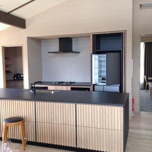 Idéer för stora industriella svart kök, med en undermonterad diskho, skåp i ljust trä, kaklad bänkskiva, grått stänkskydd, stänkskydd i porslinskakel, svarta vitvaror, ljust trägolv, en köksö och beiget golv