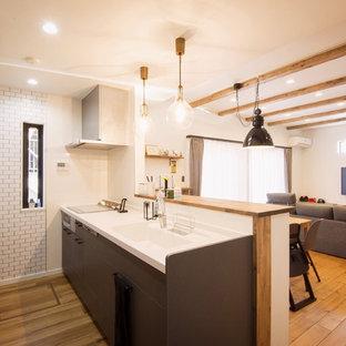 他の地域の中くらいのカントリー風おしゃれなキッチン (無垢フローリング、茶色い床、一体型シンク、フラットパネル扉のキャビネット、黒いキャビネット、茶色いキッチンカウンター) の写真
