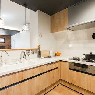 大阪の小さいコンテンポラリースタイルのおしゃれなキッチン (一体型シンク、インセット扉のキャビネット、中間色木目調キャビネット、人工大理石カウンター、白いキッチンパネル、シルバーの調理設備、無垢フローリング、茶色い床、白いキッチンカウンター) の写真