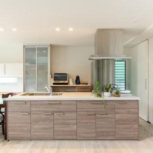 他の地域の中くらいのビーチスタイルのおしゃれなキッチン (ドロップインシンク、インセット扉のキャビネット、中間色木目調キャビネット、人工大理石カウンター、シルバーの調理設備、テラコッタタイルの床、グレーの床、白いキッチンカウンター、ベージュキッチンパネル) の写真