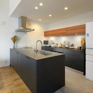 他の地域の北欧スタイルのおしゃれなペニンシュラキッチン (シングルシンク、フラットパネル扉のキャビネット、黒いキャビネット、ステンレスカウンター、コンクリートの床、グレーの床、黒いキッチンカウンター) の写真