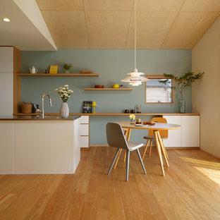 他の地域の北欧スタイルのおしゃれなキッチン (一体型シンク、フラットパネル扉のキャビネット、白いキャビネット、ステンレスカウンター、無垢フローリング、茶色い床、茶色いキッチンカウンター) の写真