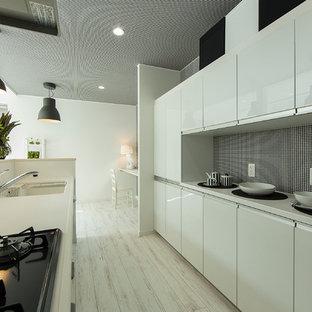 札幌のコンテンポラリースタイルのおしゃれなキッチン (アンダーカウンターシンク、フラットパネル扉のキャビネット、白いキャビネット、白いキッチンパネル、黒い調理設備、塗装フローリング) の写真