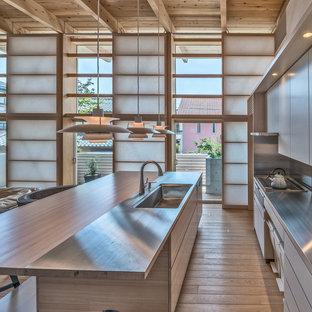 他の地域の北欧スタイルのおしゃれなキッチン (一体型シンク、フラットパネル扉のキャビネット、中間色木目調キャビネット、ステンレスカウンター、メタリックのキッチンパネル、淡色無垢フローリング、茶色い床) の写真