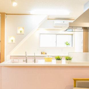 他の地域のコンテンポラリースタイルのおしゃれなキッチン (一体型シンク、フラットパネル扉のキャビネット、白いキッチンパネル、パネルと同色の調理設備、淡色無垢フローリング、アイランドなし、ベージュの床、白いキッチンカウンター) の写真