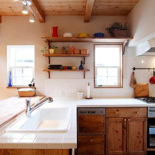 Landhausstil Küche in L-Form mit Einbauwaschbecken, Schrankfronten mit vertiefter Füllung, hellbraunen Holzschränken, Arbeitsplatte aus Fliesen, Küchenrückwand in Weiß, Rückwand aus Keramikfliesen und Halbinsel in Sonstige