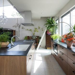 中くらいのアジアンスタイルのおしゃれなキッチン (アンダーカウンターシンク、茶色いキャビネット、黒い調理設備、磁器タイルの床、白い床、黒いキッチンカウンター) の写真