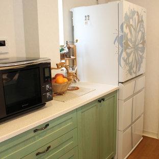 Exemple d'une cuisine américaine parallèle nature de taille moyenne avec un placard à porte shaker, des portes de placards vertess, un plan de travail en terrazzo et un îlot central.