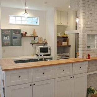 名古屋の中サイズのカントリー風おしゃれなキッチン (フラットパネル扉のキャビネット、白いキャビネット、白いキッチンパネル、サブウェイタイルのキッチンパネル、シルバーの調理設備の、アンダーカウンターシンク、テラコッタタイルの床、木材カウンター) の写真
