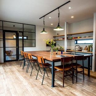 他の地域のコンテンポラリースタイルのおしゃれなキッチン (アンダーカウンターシンク、木材カウンター、白い調理設備、フラットパネル扉のキャビネット、青いキャビネット、白いキッチンパネル、淡色無垢フローリング、ベージュの床) の写真